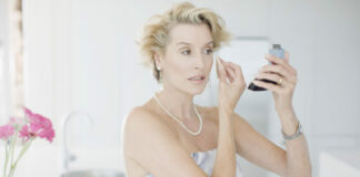 Glamorous woman putting on makeup