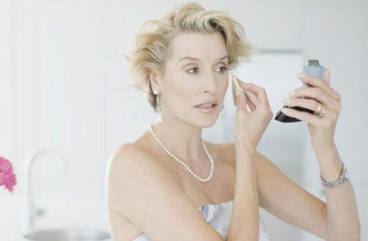 Glamorous woman putting on makeup